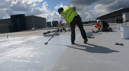 Application of the embedment coat to embed the chopped strand reinforcement layer of the Liquasil DG flat roof waterproofing system