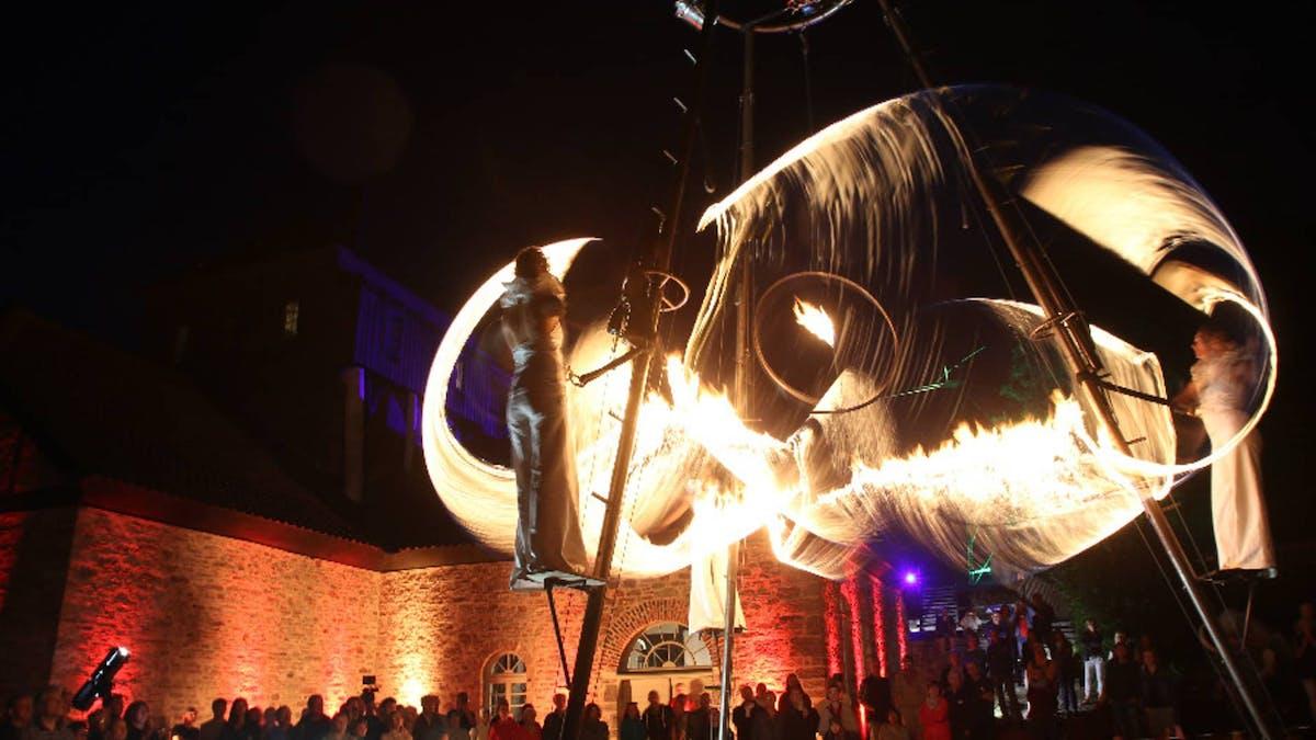 Feuershow mit Luftartistik auf einem Gerüst vor Publikum bei Event in NRW.