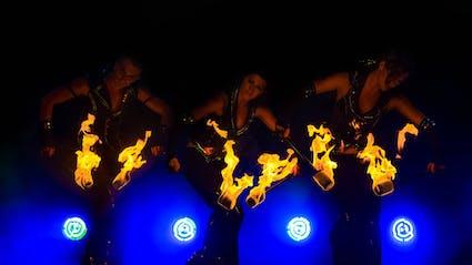 Drei Feuertänzer mit Feuerstäben und blauem Bühnenlicht.