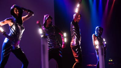 Lighting artists with LED costumes at a live show.