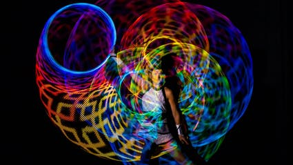 Hula-Hoop-Artistin macht Leuchteffekte.