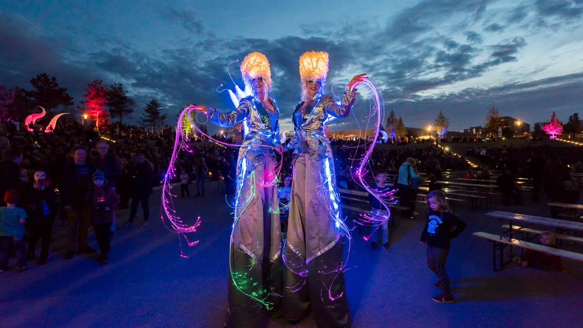 LED stilt walking-act in glowing silver costumes at a public event.