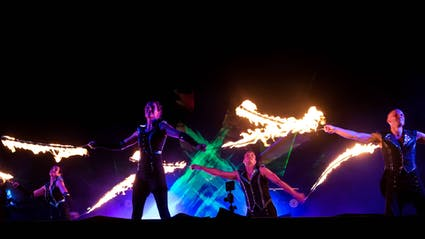 Four artists with burning ropes and Lasershow in the background.
