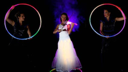 Violinist with glowing Violine and two Hula-Hoop-Performers.