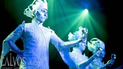 Drei Performer auf Stelzen halten eine Kristallkugel in der Hand.