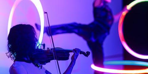 Geigerin spielt auf Bühne und im Hintergrund Artistin mit 4 LED-Hula Hoops am Körper.