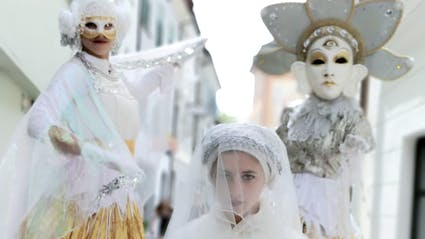 Walkact with three artists in white costumes.