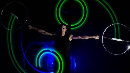 Poi-Performer spielt mit ausgestreckten Armen und erzeugt zwei grüne Kreise.