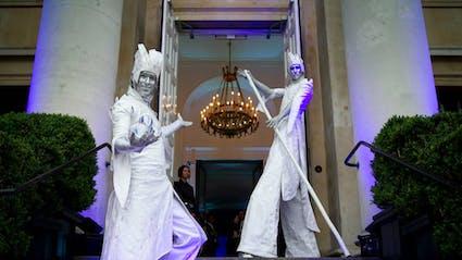 Zwei Stelzenläufer begrüßen die Gäste vor einem großen Eingang.