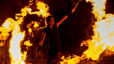 Fire artist at fire show with large flame effects.