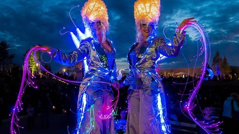 Zwei Stelzen Walkacts in leuchtenden silbernen Kostümen.