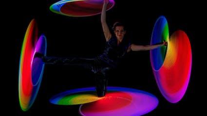Hula-Hoop-Show mit vier leuchtende Ringen um die ausgestreckten Arme und Beine der Artistin.