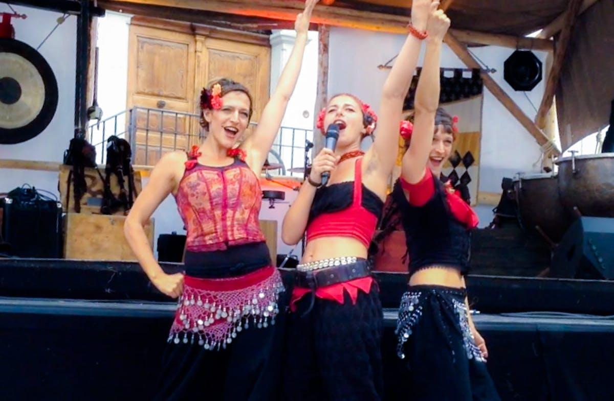 Strassenshow mit drei Gauklerinnen, die mit den Fingern in die Luft zeigen.
