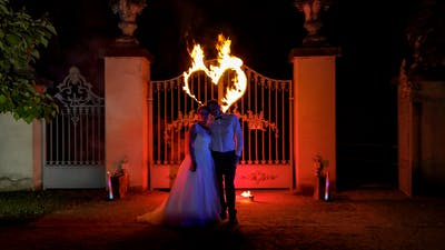 Bridal couple at fire show in front of a burning heart.
