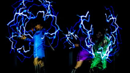Three blurred performers, who create bright flashs.