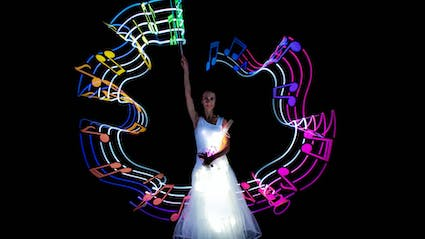 Violinist who draws Light-Painting in shape of notes around her.