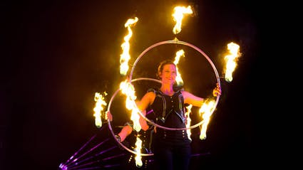 Artist with firestaff and fire Hula-Hoop and laser.