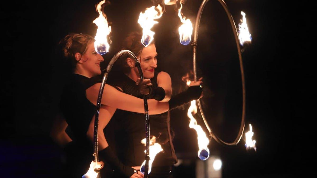 Zwillinge bei einer Feuershow mit Feuer Hula-Hoop.