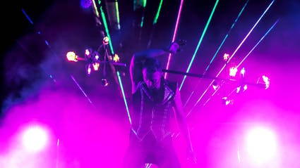 Performer mit Feuerstab vor Laserlicht.