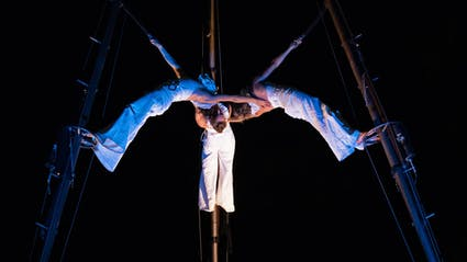 Three aerial acrobats bend their backs to each other.