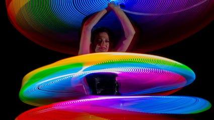 Leuchtende Multi-Hula-Hoops um den Körper der Artistin.