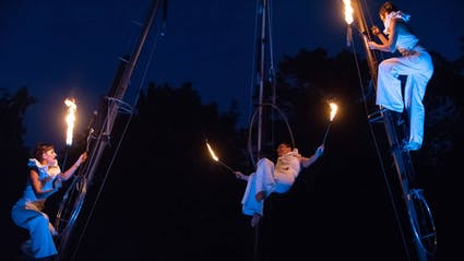 Big fireshow with three aerial acrobats holding firepoi at an event in NRW.