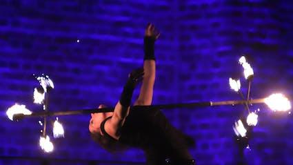 Performerin balanciert Feuerstab auf der Brust.