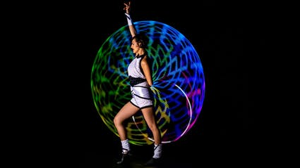 LED-Hula-Hoop Artistin in Disko Pose.