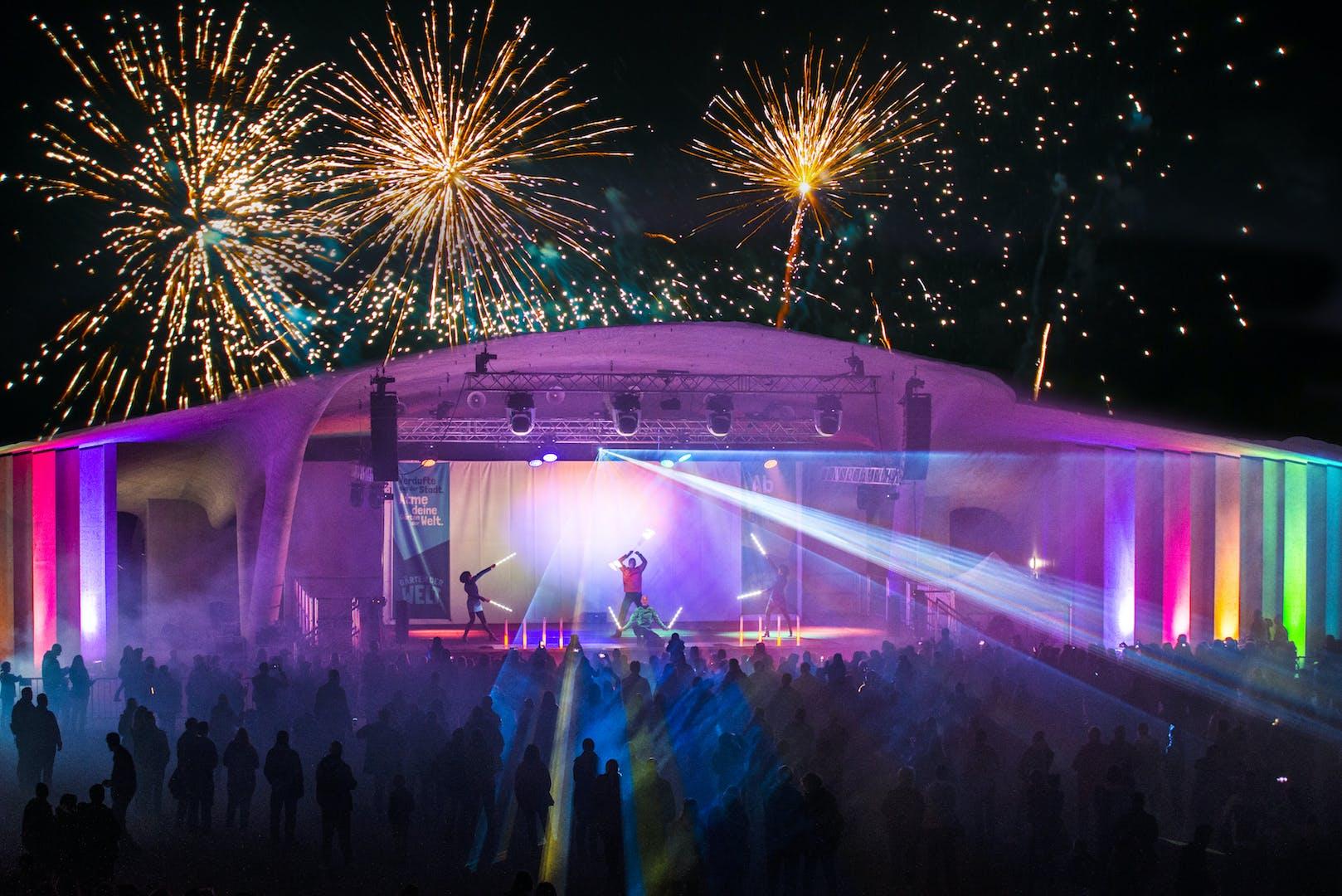 Outdoorbühne mit Artisten auf der Bühne und Feuerwerk und Lasershow im Hintergrund und vielen Zuschauern.