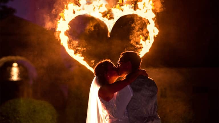 Romantic wedding fire show with burning heart.