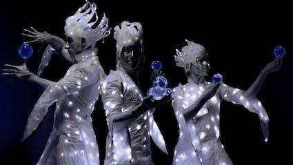 Drei Performer in leuchtenden silbernen Kostümen spielen Kontaktjonglage.