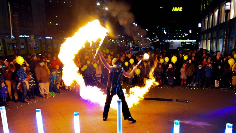 Solo-Fireshow with bowing performer holding firepoi in the hand.