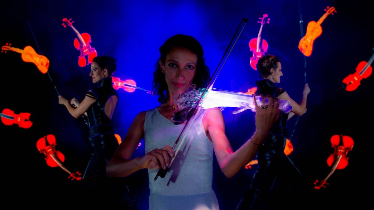 Violinist with Live-Violine and in the background Poi-Performer with glowing Violines.