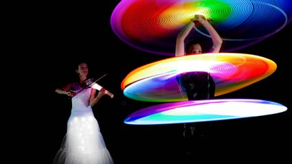 Violinist and Hoop-Dancer with three glowing Hoops.
