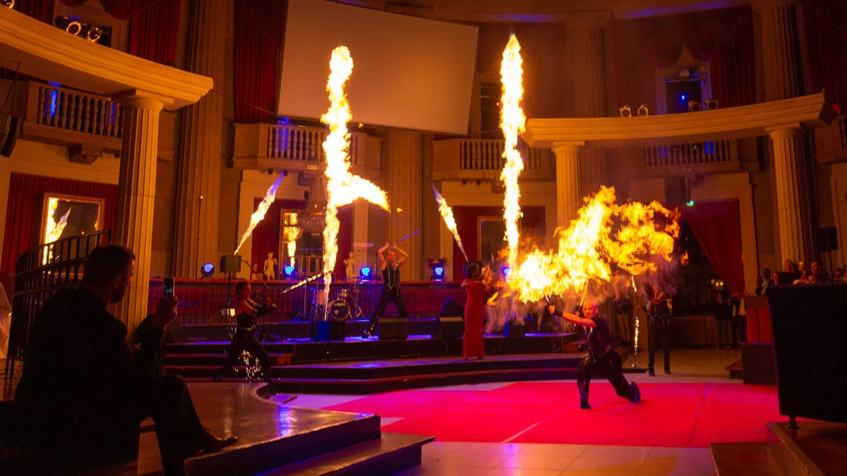 Fireshow with big fire effects, flamethrower and fire artists in a columned hall.