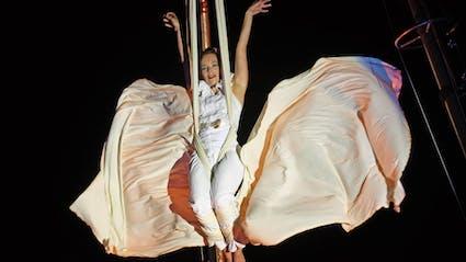 Luftartistin hängt mit wehendem Kostüm an einem Seil.