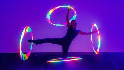 In Glow-Show spielt Hula-Hoop-Artist vier Hoops an ausgestreckten Armen und Beinen.