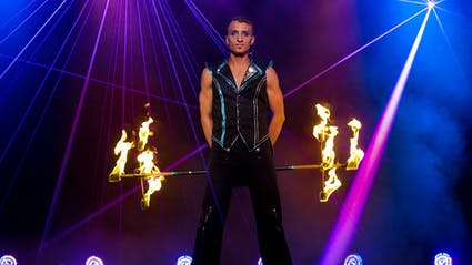 Artist mit Feuerstab und Laser im Hintergrund.