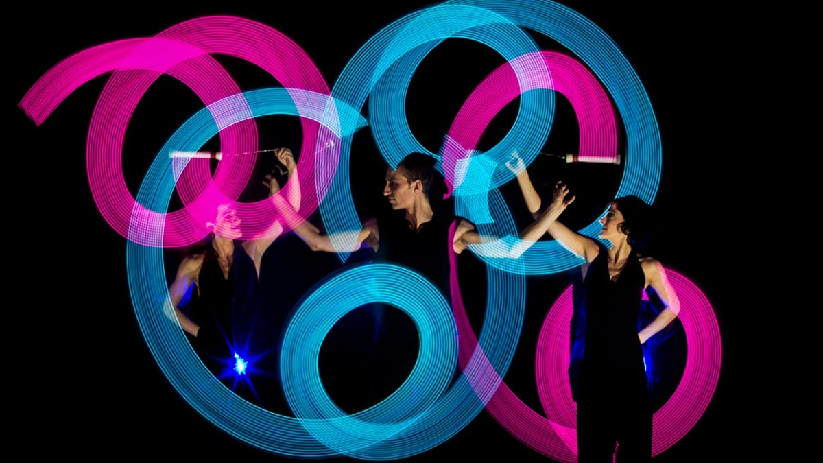 Drei Artisten, die Poi mit Lichtkreisen um sich herum schwingen.