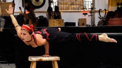 Artistin balanciert in einer Straßenshow auf einem Arm.
