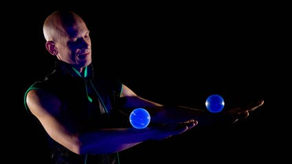 Contact juggling with two crystal balls on the forearms.