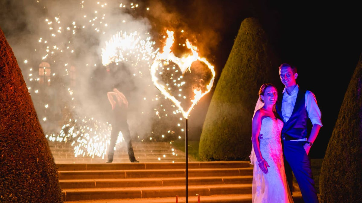 Fire show at a wedding with burning fire-heart and a fire-artist.
