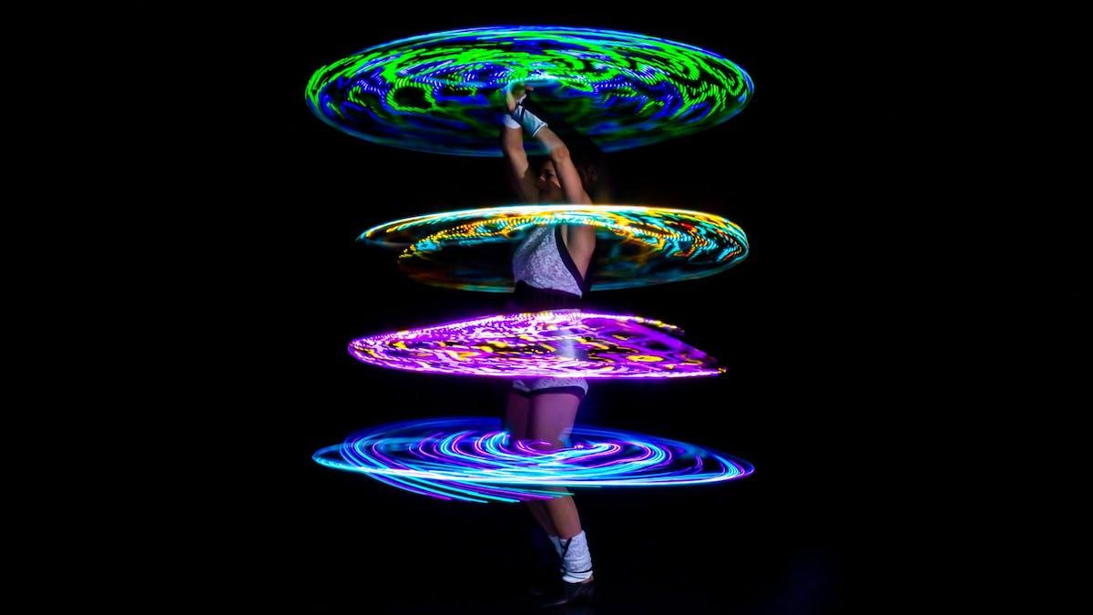 Showact mit vier leuchtenden LED-Multi-Hoops um den Körper der Artistin.