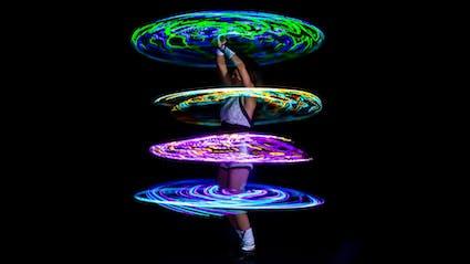 Hula-Hoop-Artist mit vier leuchtenden LED-Hoops um ihren Körper.