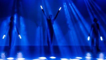 Drei Künstler mit Lichtstäben in den Händen auf einer Bühne mit blauen Lichtstrahlen.