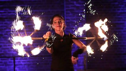 Performerin mit Feuerstab.