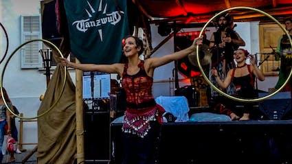 Gauklerin hält zwei Hula-Hoops in den Händen.