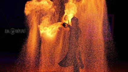 Feuerartistin steht in großem Funkenschweif.