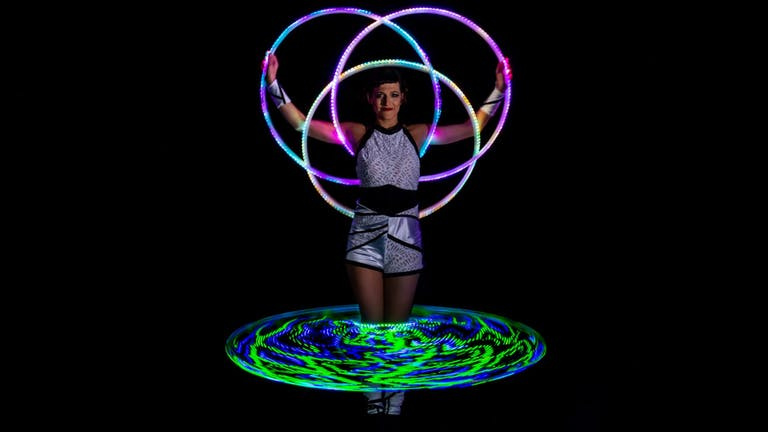 Showact with four glowing LED-Multi-Hoops around the artists body.