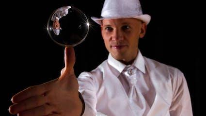 Contact juggler balances crystal ball on the thumb.